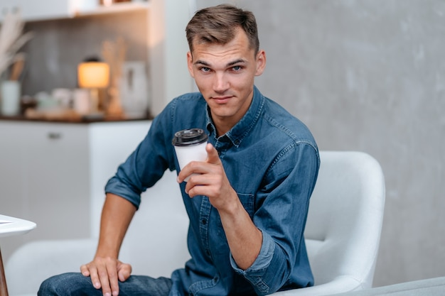 Улыбающийся молодой человек с чашкой кофе, указывая на вас. домашняя жизнь.