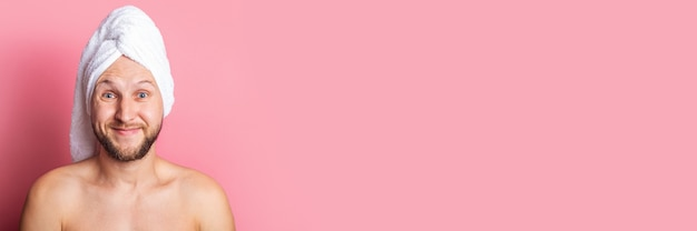 ピンクの背景に彼の頭にタオルで若い男を笑顔