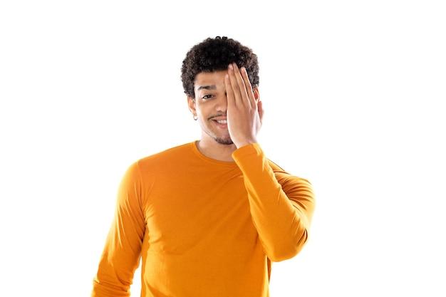 白い背景で隔離のオレンジ色のセーターを着てアフロ髪の若い男を笑顔