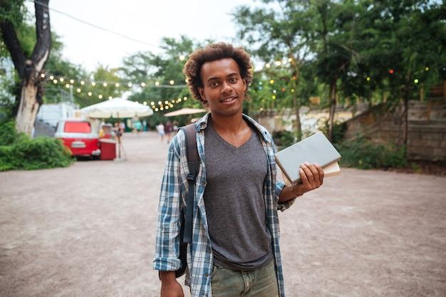 Улыбающийся молодой человек с рюкзаком стоит и держит книги на открытом воздухе