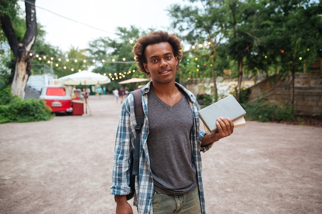 Smiling young man with backpack standing and holding books outdoors