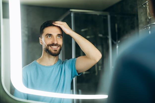 Улыбающийся молодой человек с голубыми глазами трогает его волосы перед зеркалом утром