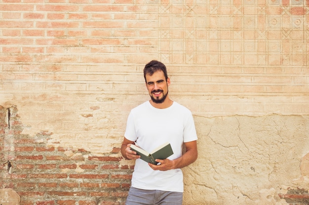 Smiling young man with book in front of wall