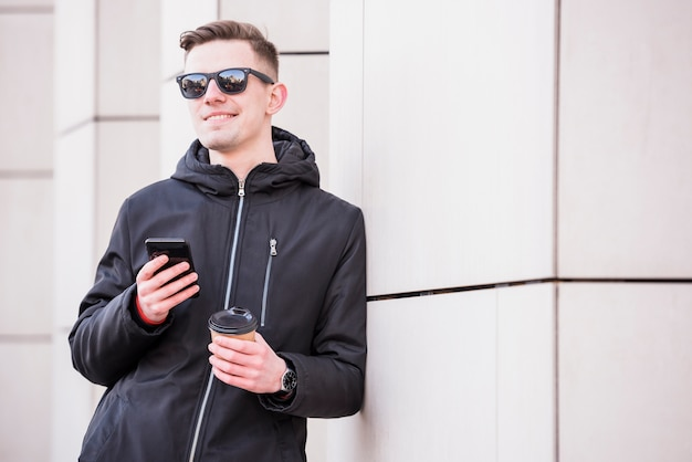 Smiling young man with holding mobile in hand holding takeaway coffee cup