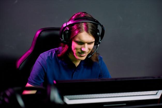 Улыбающийся молодой человек с длинными волосами играет в сетевую игру во время разговора с игровым союзником через гарнитуру с микрофоном