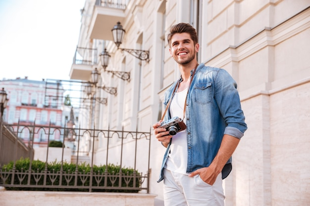 Smiling young man with old vintage photo camera standing in the city