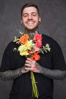 Smiling young man with pierced ears and nose holding bouquet in hand looking at camera