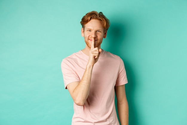Smiling young man with red hair and beard sharing a secret, showing taboo gesture and grinning, shushing you to be quiet, standing over turquoise background.