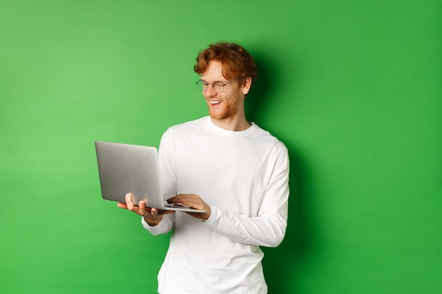 Smiling young man with red hair, wearing glasses, working on laptop and smiling, standing over green background.