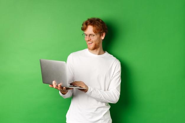 빨간 머리를 가진 젊은 남자 웃 고, 안경을 쓰고, 노트북에서 작업 하 고 웃 고, 녹색 배경 위에 서.