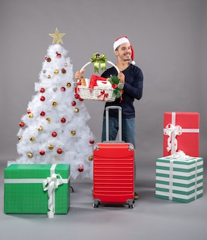 Smiling young man with santa hat holding gift basket with both hands near xmas tree on grey