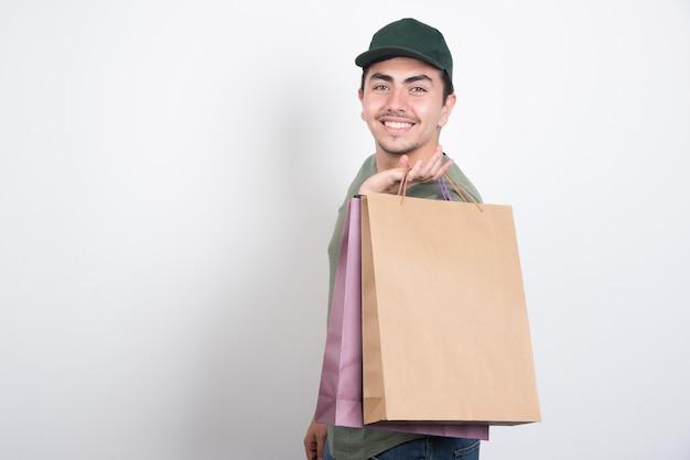 흰색 배경에 쇼핑 가방과 함께 웃는 젊은 남자.