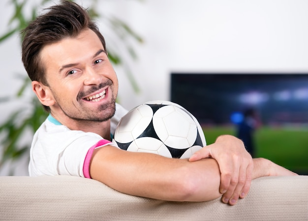 Smiling young man with soccer ball while watching the game.