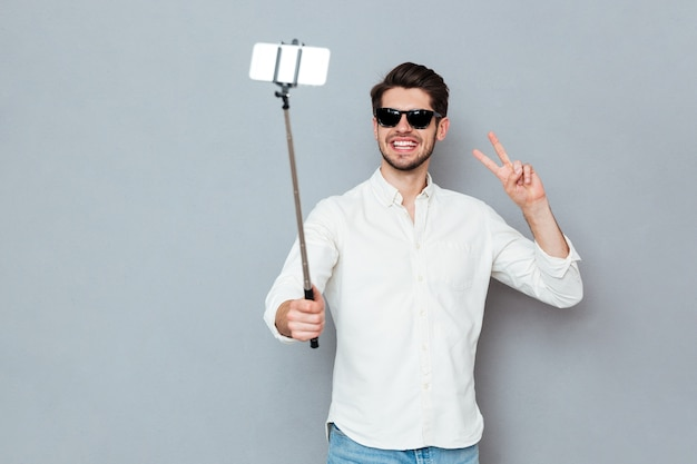 Smiling young man with sunglasses taking photos with smartphone and selfie stick isolated