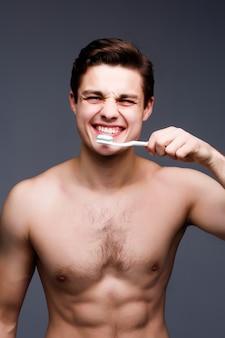 黒い壁に分離された歯ブラシクリーニング歯と笑顔の若い男