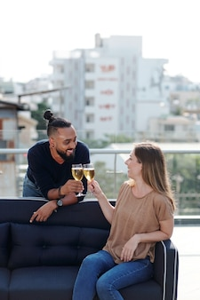 Smiling young man and woman drinking champagne and flirting at rooftp party