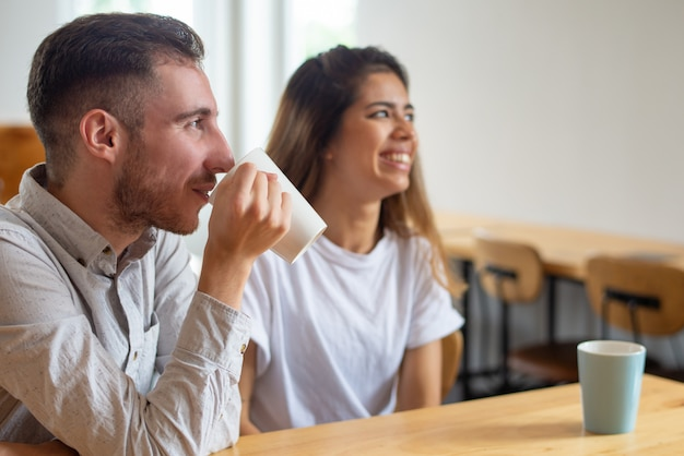 Smiling young man and woman drinking tea in cafe