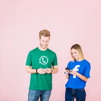 Smiling young man and woman using cellphone over pink backdrop