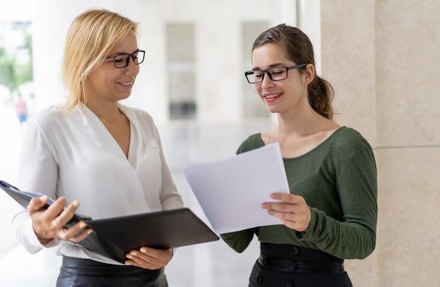 Улыбаясь молодой менеджер дает документ доклад