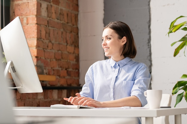 Smiling young manager or other specialist reading online information on computer screen by workplace