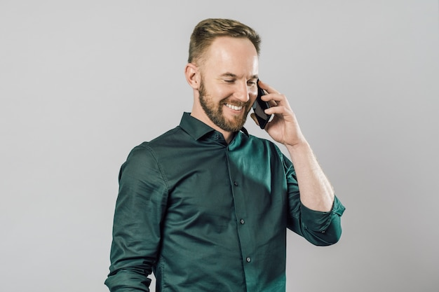 Smiling young mantalking on mobile phone