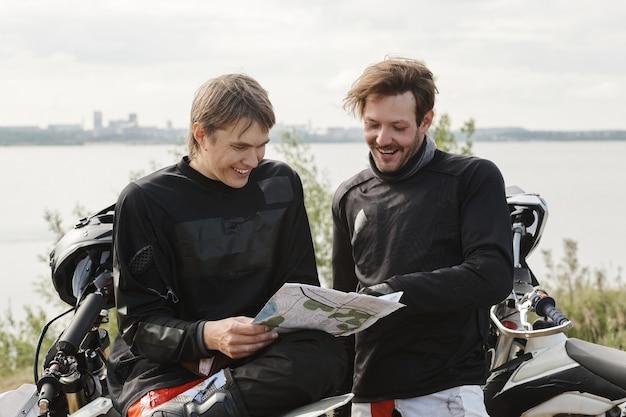 Улыбающиеся молодые люди в мотоциклетных доспехах, стоящие у озера и использующие карту при выборе маршрута мотоцикла