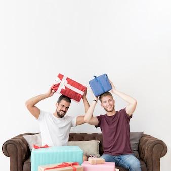 Giovani sorridenti che si siedono sui contenitori di regalo della tenuta del sofà sulla sua testa