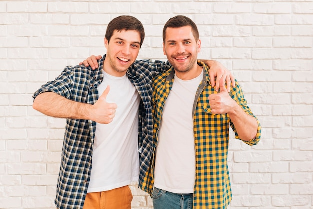 Smiling young men with their arms around their shoulder showing thumb up sign