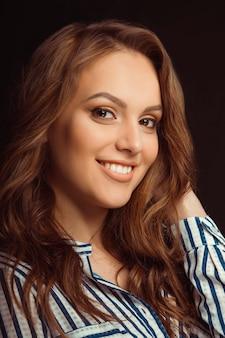 검은 배경 위에 스튜디오에서 포즈를 취하는 셔츠에 웃는 젊은 모델
