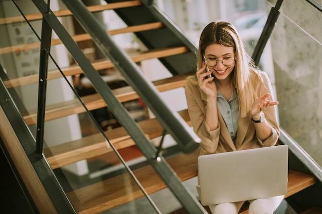 Улыбающаяся молодая современная деловая женщина сидит на лестнице в офисе, работает над ноутбуком и разговаривает по мобильному телефону