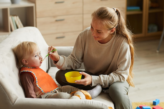 Smiling young mother feeding child with spoon during lunch time at home