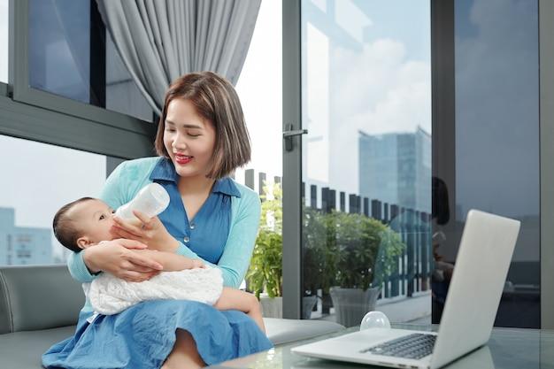 Улыбающаяся молодая мать кормит дочь смесью во время перерыва после работы на ноутбуке дома