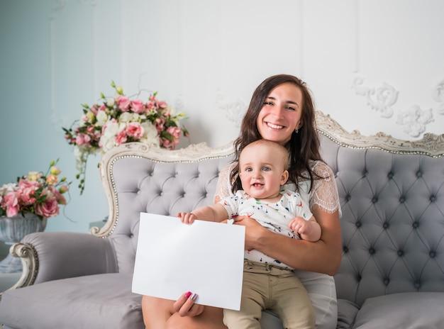 笑顔の若い母親は、居心地の良い美しい部屋のソファに座っている小さな魅力的な子供と空の紙を手に持っています