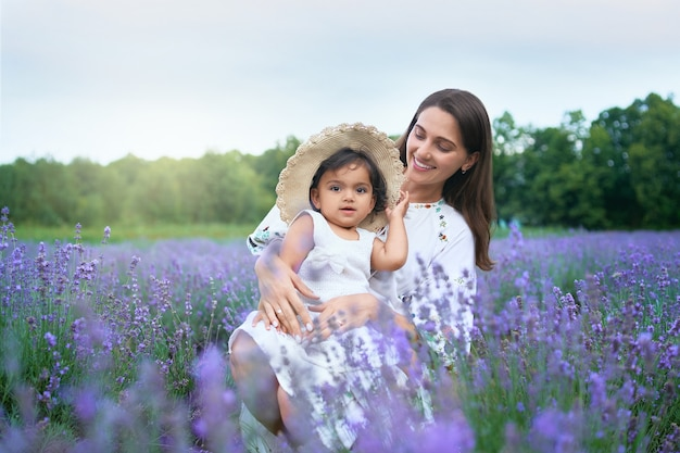 Smiling young mother posing with kid in lavender field
