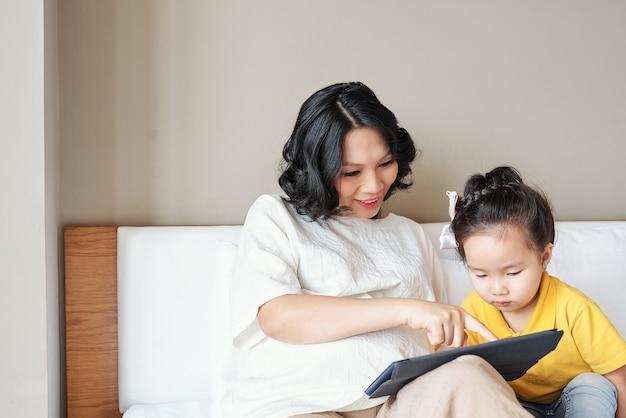 Улыбающаяся молодая мать показывает своей маленькой дочери образовательное приложение на планшетном компьютере