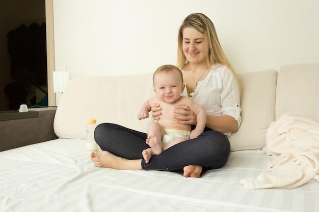 그녀의 아기와 함께 침대에 앉아 웃는 젊은 어머니