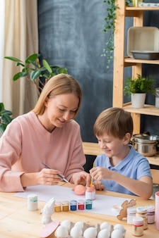 Smiling young mother sitting at table and painting eggs for easter together with cute son