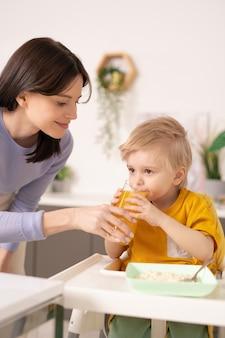 유아용 의자에 서서 부엌에서 작은 아들에게 신선한 주스를주는 웃는 젊은 어머니