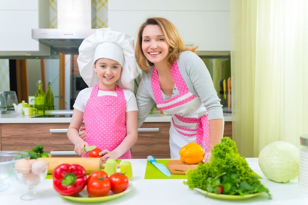 Sorridente giovane madre con la figlia in grembiule rosa cucinare le verdure in cucina.