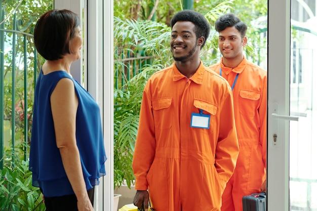 Улыбающиеся молодые многонациональные дворники в оранжевых трико, стоящие у входа в дом и входящие в дом клиентов, приветствуя их зрелую женщину