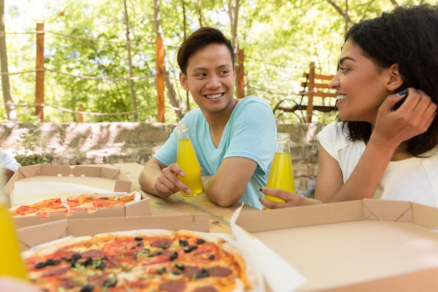 Smiling young multiethnic friends students outdoors drinking juice eating pizza.