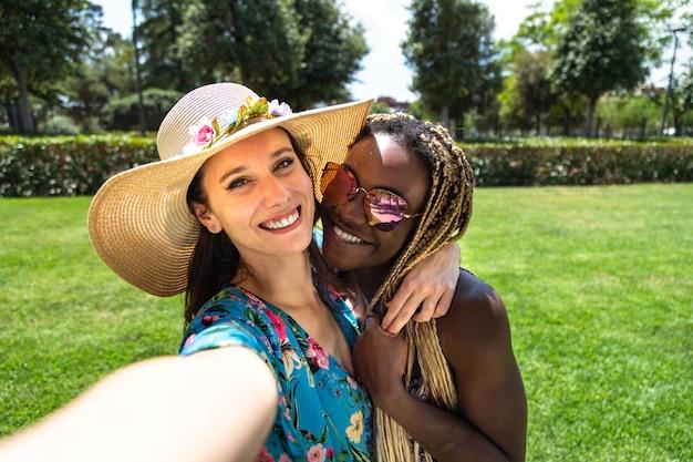 Улыбающаяся молодая многорасовая женская пара делает селфи в парке во время летних каникул лгбт