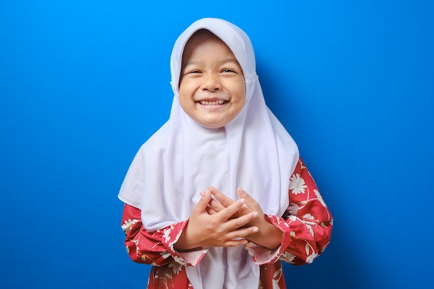 Smiling young muslim girl in hijab red clothes, looking camera isolated on blue wall background, studio portrait. people religious lifestyle concept.