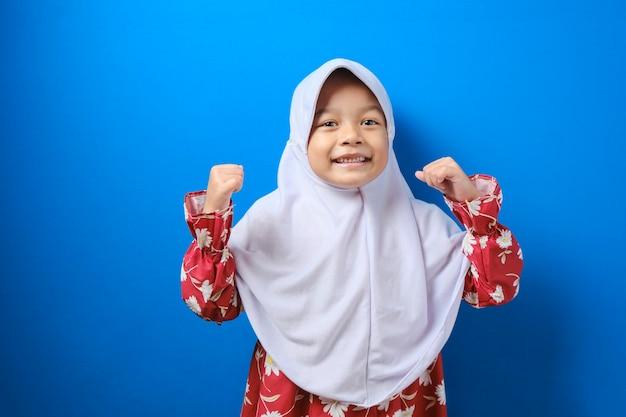 히잡 빨간 옷을 입은 웃고 있는 어린 이슬람 소녀, 파란 벽 배경, 스튜디오 초상화에 격리된 카메라를 보고 있습니다. 사람들이 종교적인 라이프 스타일 개념입니다.