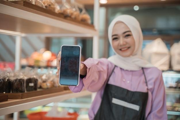 ヒジャーブと笑顔の若いイスラム教徒の女性はカメラに彼女の携帯電話の画面を表示します