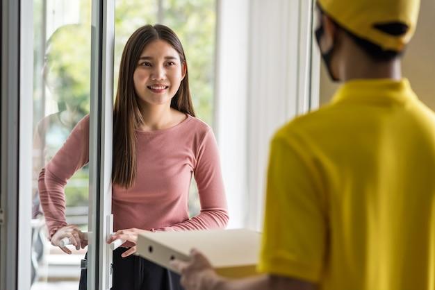 Улыбающийся молодой офисный бизнес-леди принимает заказ еды от доставщика в маске для лица