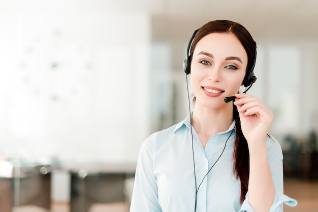 Smiling young office worker with a headset  answering in a call center, woman talking with clients. portrait of an attractive customer and technical support representative