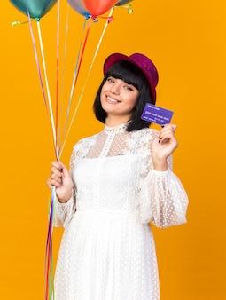 Улыбающаяся молодая тусовщица в партийной шляпе держит воздушные шары и показывает кредитную карту, изолированную на оранжевой стене