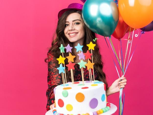 Улыбающаяся молодая тусовщица в партийной шляпе держит воздушные шары и протягивает торт со звездами к камере, глядя в камеру, изолированную на розовой стене с копией пространства