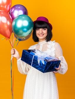 Sorridente ragazza di partito che indossa cappello da festa tenendo palloncini e allungando il pacchetto regalo isolato sulla parete arancione